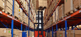Man operating a forklift, lifting up a box to put into a racking storage system provided by Stormor Systems